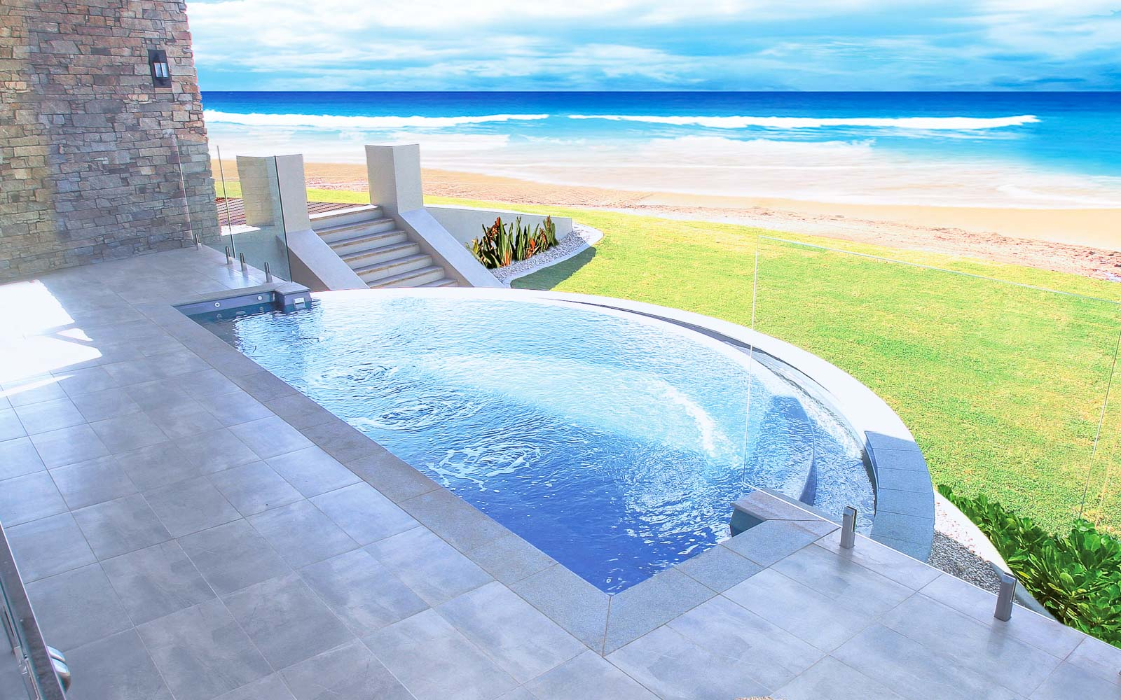 Leisure Pools Horizon fiberglass in-ground swimming pool with an infinity edge