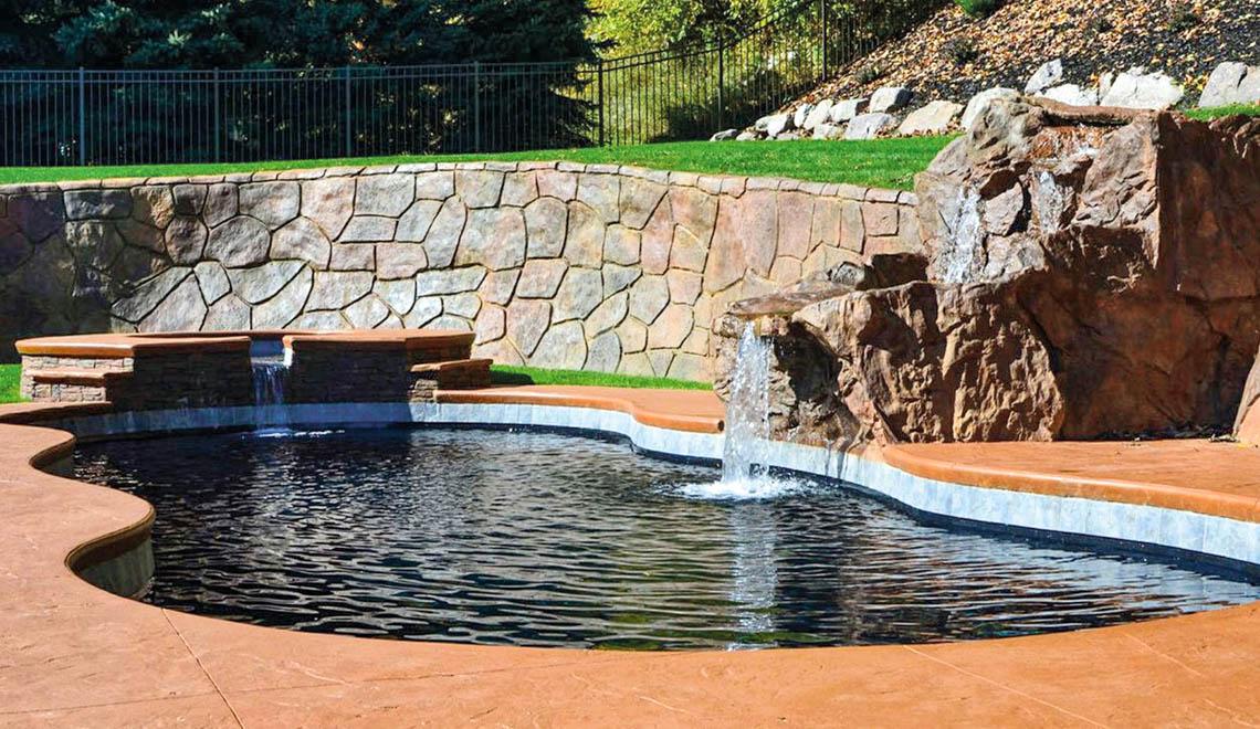 Leisure Pools Mediterranean fiberglass freeform swimming pool with wrap-around bench